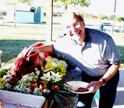 Remington VP Paul Cahan mugs with the roast pig at the final picnic on Friday afternoon.
